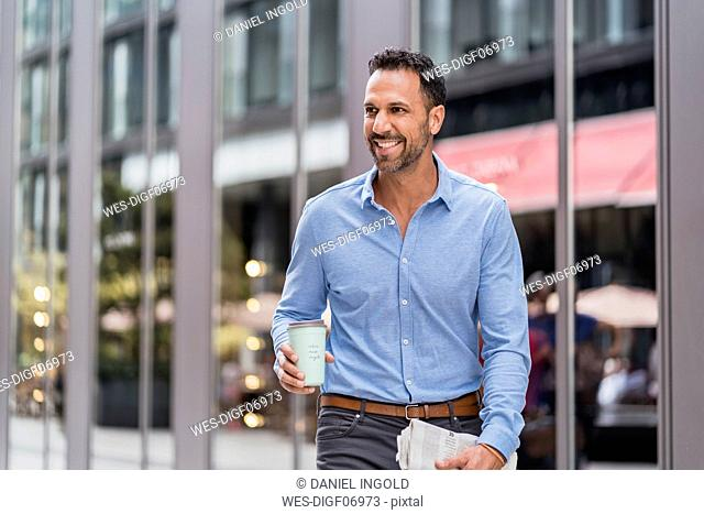 Businessman with takeaway coffee and newspaper in the city on the go