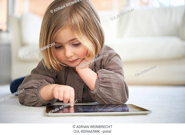Girl lying on floor using digital tablet