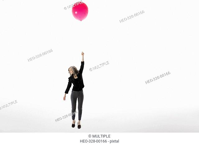 Woman holding red balloon, floating against white background