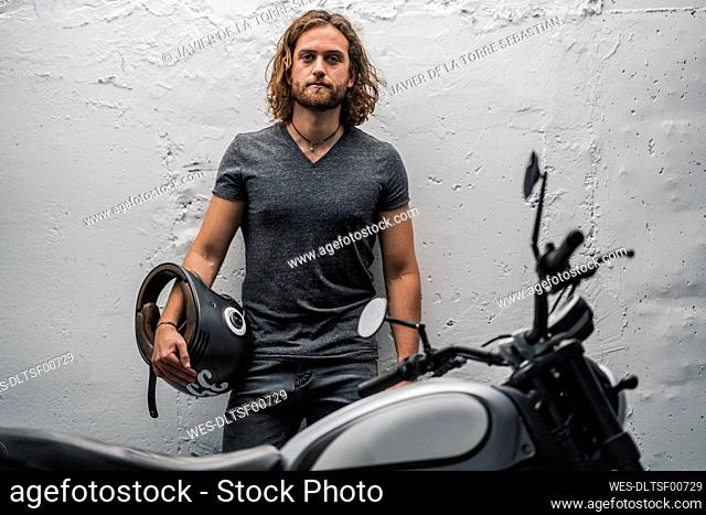 Young man with helmet leaning on white wall behind motorcycle
