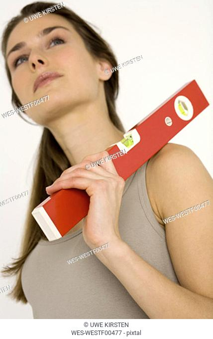 Young woman holding red spirit level looking away, close-up