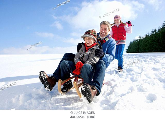 Father and son sledding down snowy hill