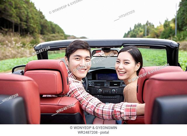 Back portrait of young smiling couple in a car looking back