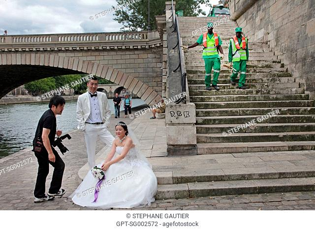 CHINESE BRIDE AND GROOM POSING FOR THEIR WEDDING PHOTO AND CITY CLEANING OPERATIVES ON THE POINT OF ILE SAINT-LOUIS, PARIS 75, FRANCE