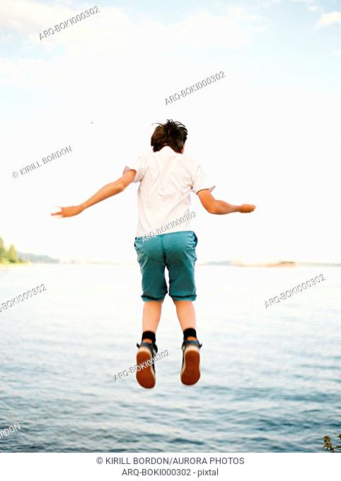 Rear view shot of boy in t-shirt and shorts jumping against sea