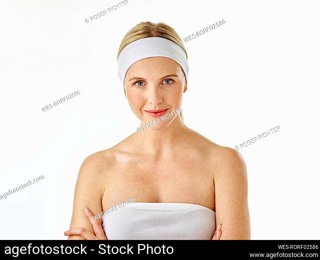 Woman wearing headband and towel staring while standing against white background