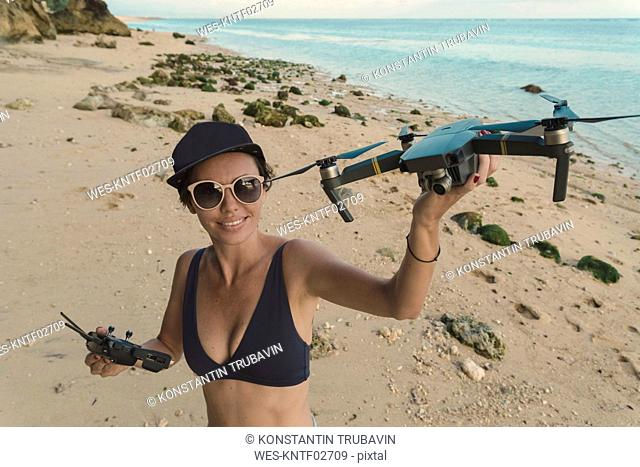 Indonesia, Bali, Nusa Dua, woman holding drone at the beach