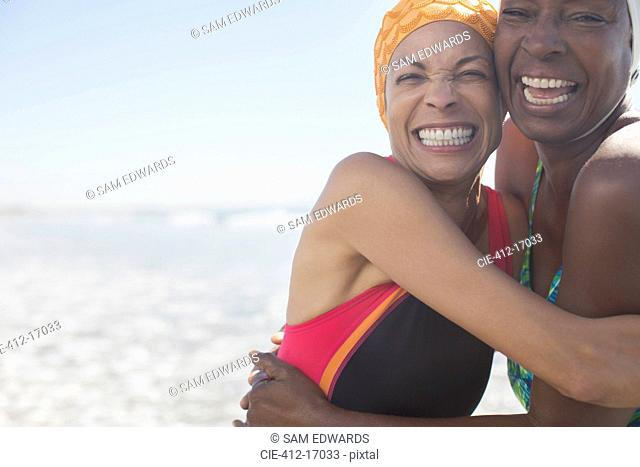 Enthusiastic women hugging on beach