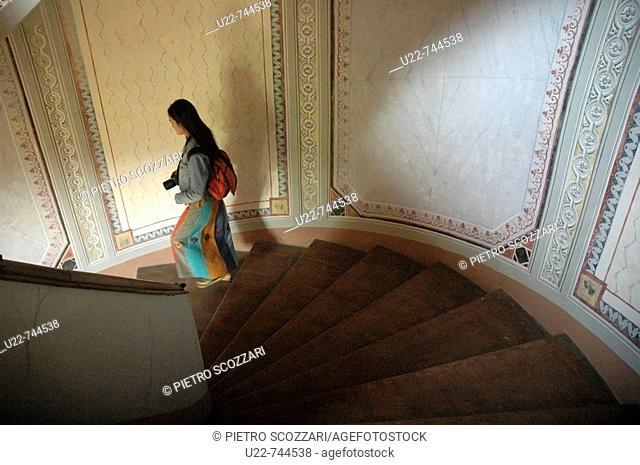 Vignola Modena, Italy, an Asian tourist along Palazzo Barozzi's winding staircase