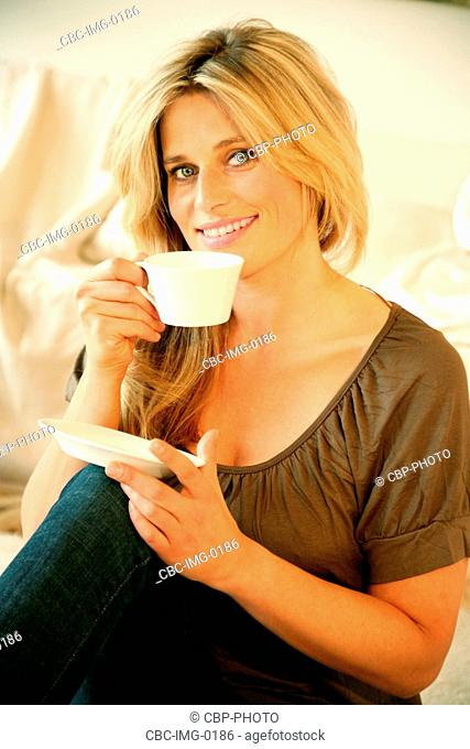 Portrait of Young Woman Having a Cup of Coffee, Sitting on Sofa