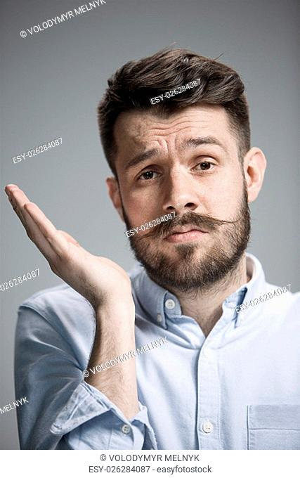 Man wearing a blue shirt is looking bored. Over gray background
