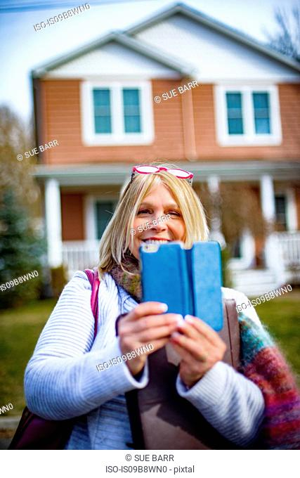 Portrait of mature woman outside house photographing on smartphone