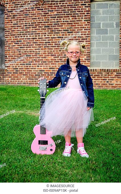 Young girl wearing tutu and denim jacket, holding guitar
