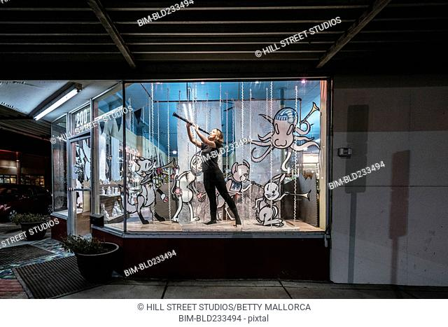 Girl playing clarinet in display window of music store