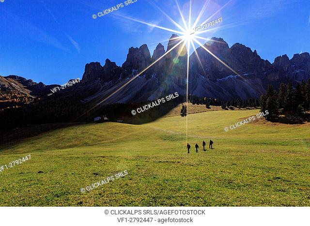 Hikers crossing the green pastures of Malga Glatsch illuminated by sunbeams. Funes Valley South Tyrol Dolomites Italy Europe