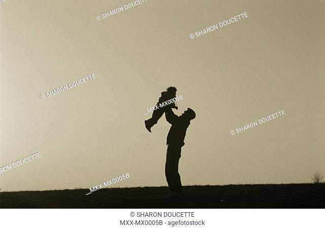 Father and child, sunset silhouette