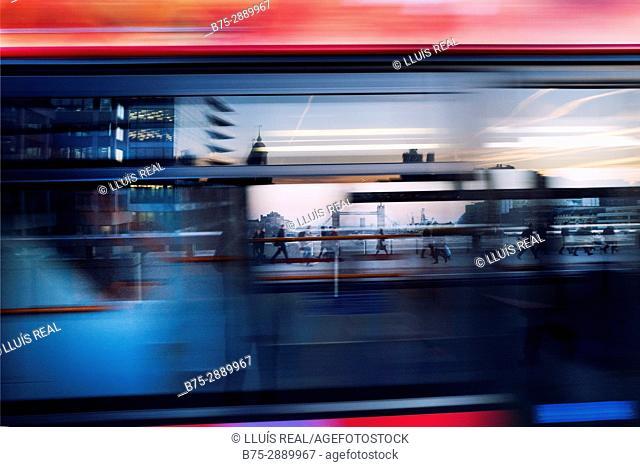People walking across the London Bridge, seen through a moving bus in London, England, UK