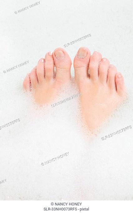 Woman?s feet in bubble bath