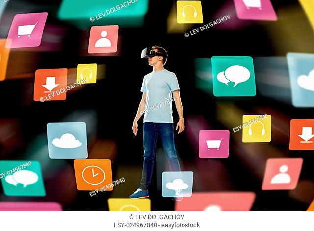 3d technology, gaming, augmented reality, cyberspace and people concept - happy young man in virtual reality headset or 3d glasses with menu icons over black...