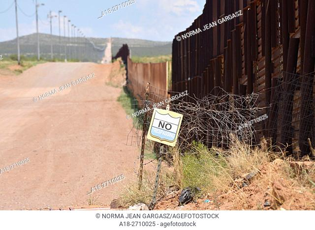 The international border between Naco, Arizona, USA and Naco, Sonora, Mexico is indicated by a metal wall. A sign prohibits trespassing on to private property...