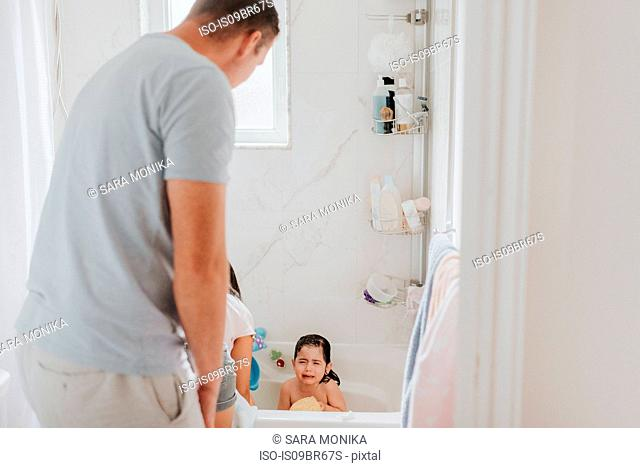Parents with crying daughter at bath time