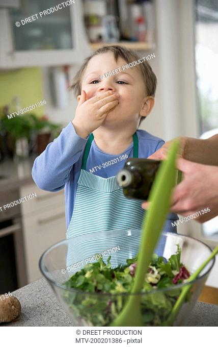 Boy helping mother in preparing salad, close up