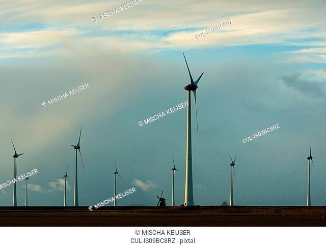 Modern wind turbines around lone traditional windmill, Delfzijl, Groningen, Netherlands