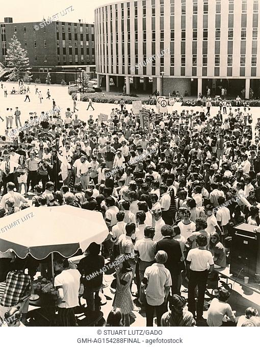 Students gather in a large group during a student strike to protest against the Vietnam War and US actions in Cambodia, some wearing hippie attire and carrying...