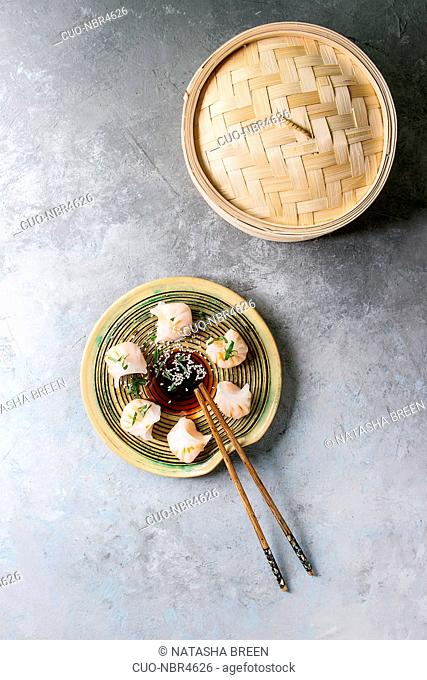 Asian steam potstickers dumplings stuffed by shrimps, served on ceramic plate with soy sesame sauce, chopsticks, bamboo steamer over grey texture background