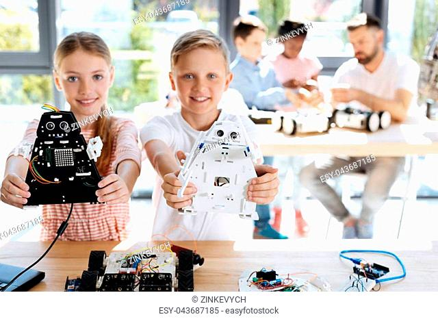 Talented children. Charming joyful brother and sister standing near the working table during their robotics workshop and showing their robot models