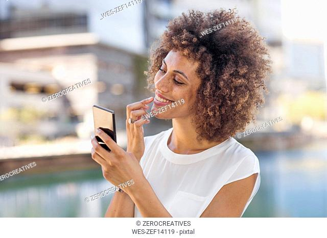 Young woman preparing for selfie, checking make up