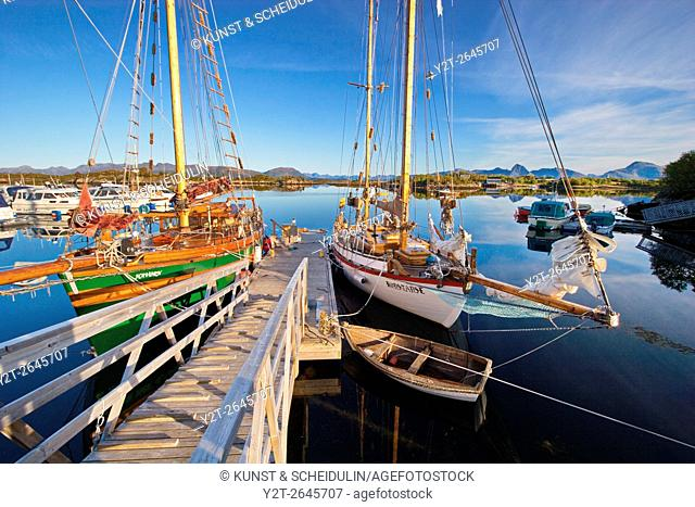 Wooden sailing ships are moored in the small boat harbor in Ringstad on island Langøya (Vesterålen) in northern Norway