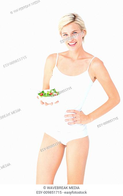 Beautiful fit woman holding a bowl of salad