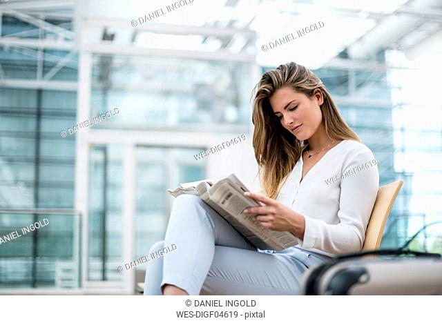Young businesswoman sitting outdoors with suitcase reading newspaper