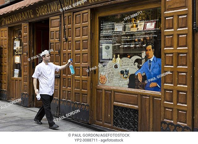Madrid, Spain: A worker cleans the front window of Restaurante Sobrino de Botín. Originally founded in 1725 as Casa Botín