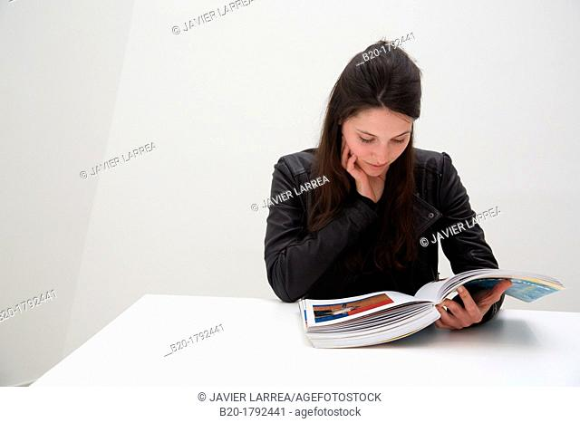 Young woman looking at exhibition catalog. David Hockney, 'A Bigger Picture' exhibition, Guggenheim Museum, Bilbao, Biscay, Basque Country, Spain