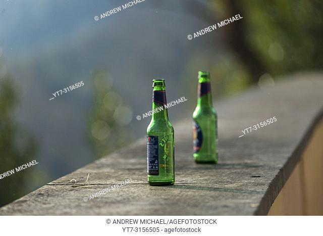Two empty green beer bottles abandoned on top of a wall on Janiculum hill, Rome, Italy