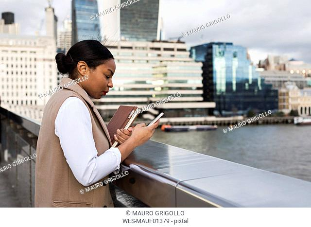 UK, London, businesswoman standing on bridge using cell phone