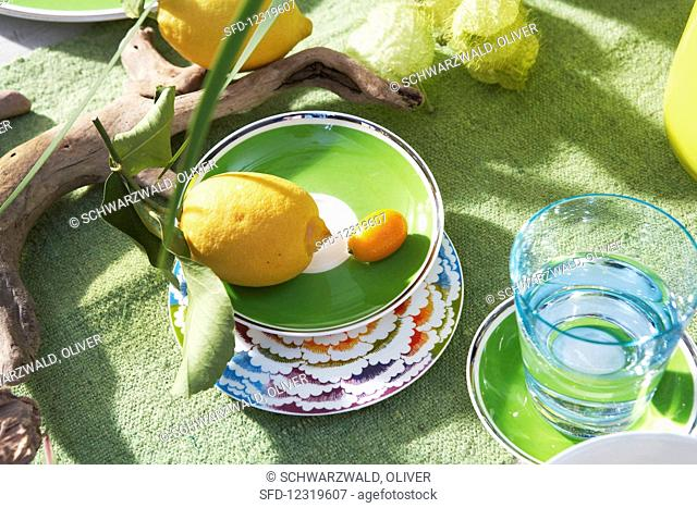 A lemon and a kumquat in a green bowl next to a water glass