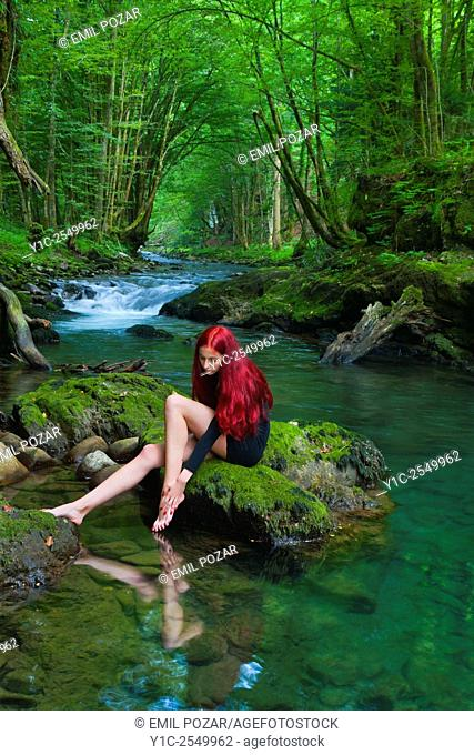 Red-haired young woman on small forest river