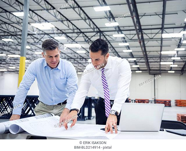 Caucasian architects working in warehouse