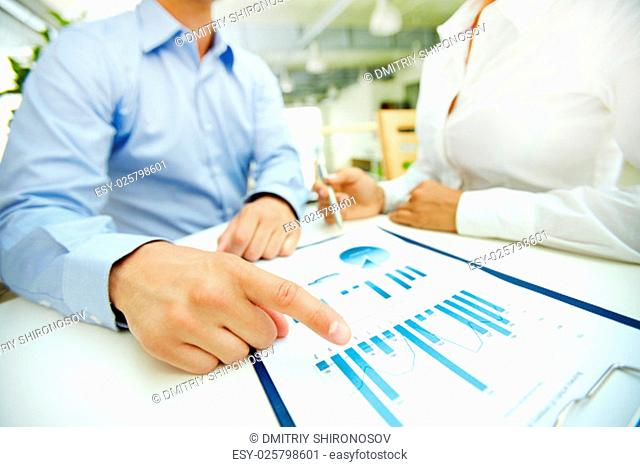 Businessman pointing at chart during discussion of document
