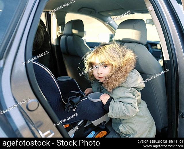 Little girl getting in her carseat