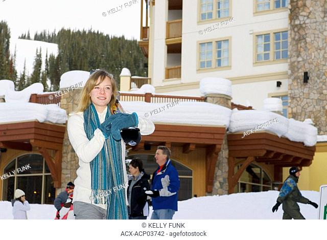A young women carries her skis through the Village at Sun Peaks Ski Resort just North of Kamloops, British Columbia, Canada