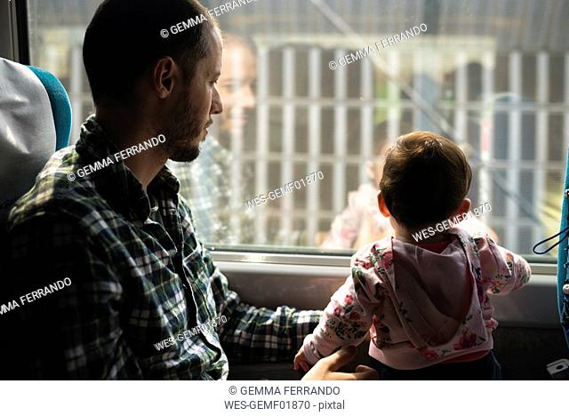 Father and baby girl traveling by train looking out of window