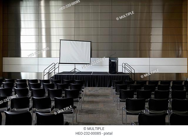 Chairs and projection screen in empty auditorium
