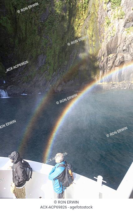 People and a rainbow in the mist of Stirling Falls on a boat tour on Milford Sound, New Zealand