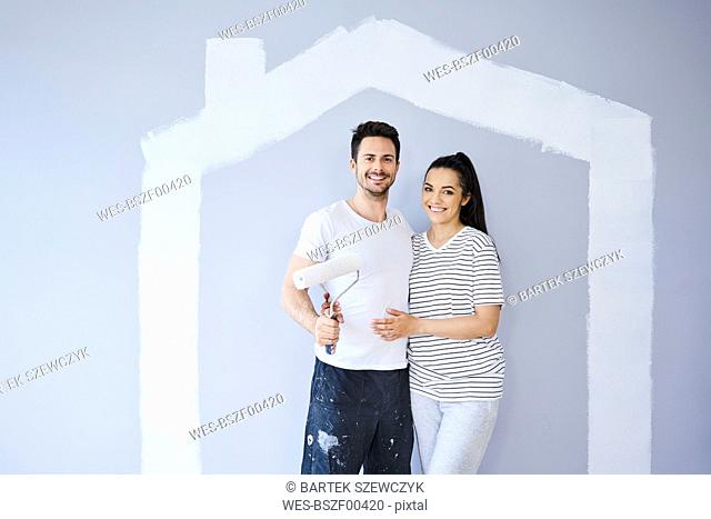 Portrait of happy couple painting in new apartment with house shape on wall