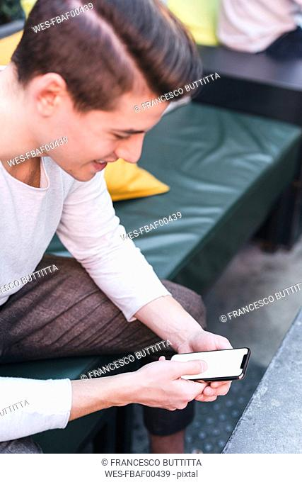 Smiling young man sitting on couch in a cafe using cell phone