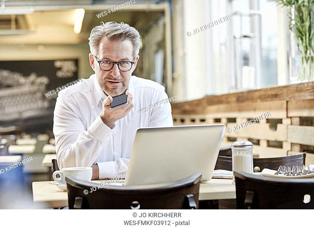 Mature businessman in cafe using laptop and cell phone